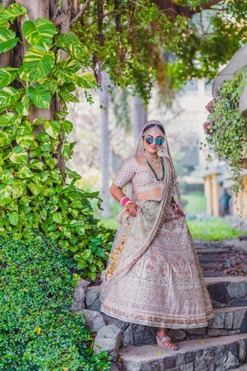 Bride in off white bridal lehenga and reflectors