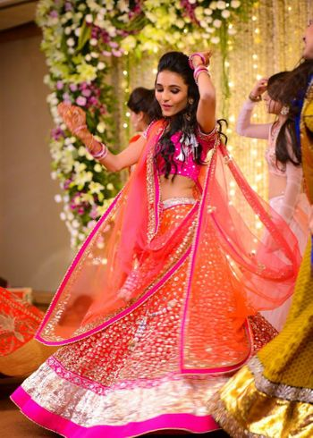 Photo of Orange Sequins Twirling Lehenga with Gold Border