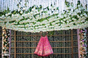 Bright pink bridal benarasi lehenga on hanger