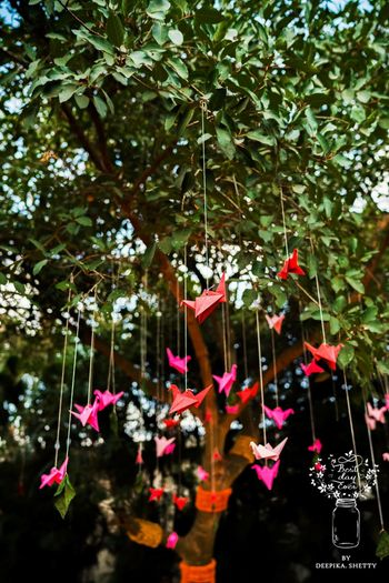 Colourful origami birds hanging from a tree decor