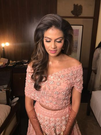 Photo of Peach lehenga with off shoulder blouse and one sided hairstyle
