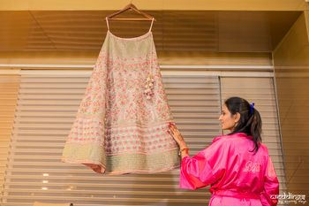Photo of Getting ready shot idea with lehenga on hanger and bride in robe