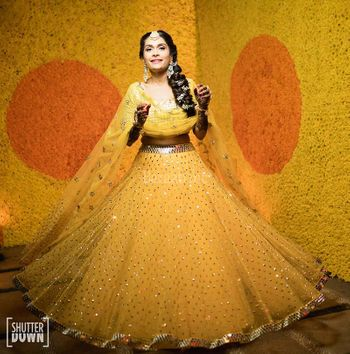 Photo of A bride in a yellow lehenga twirling on her mehendi day