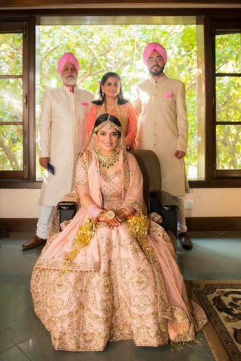 Beautiful family portrait with bride in a peach lehenga and emerald jewellery