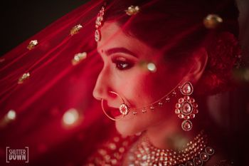 Bridal portrait with red dupatta as veil