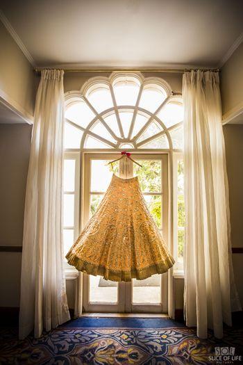 Peach bridal lehenga on hanger against window