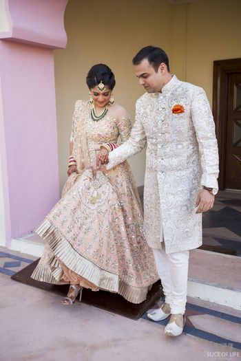 Bride in light peach girly engagement lehenga