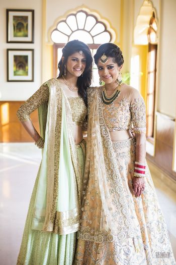 Bride and sister in girly pastel lehengas