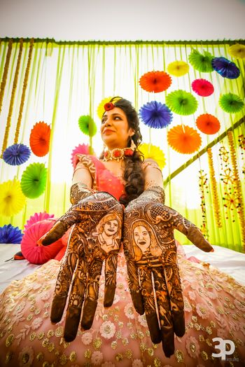 Bride showing off mehendi with portraits