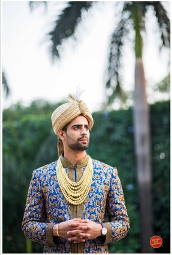 Unique groom look with blue sherwani and gold accessories