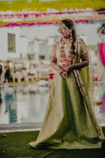A bride-to-be in a green lehenga and pink floral jewellery for her mehndi