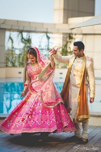 Couple shot with bride in pink ombre lehenga