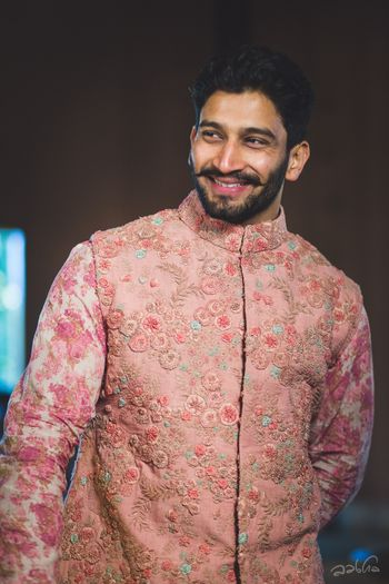 Stunning pink kurta with a floral work jacket on it for the groom on wedding day