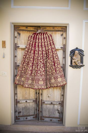 Photo of Maroon and gold bridal lehenga on hanger