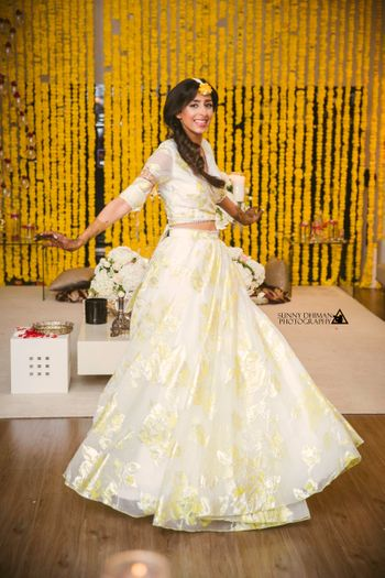 Bride twirling in simple off white organza lehenga