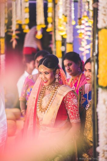 Photo of South Indian bride entering in gold saree and red blouse