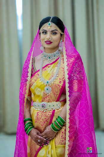 South Indian bride in yellow saree and diamond jewellery