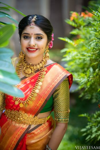 A south Indian bride wearing a kanjeevaram saree and gold, temple jewelry