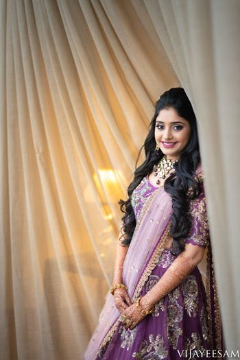 Sangeet bridal look with open hair and purple lehenga