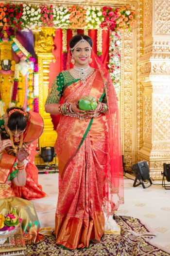 Bride in orange kanjivaram saree with green blouse