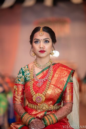 Bride in orange and green saree with layered temple jewellery