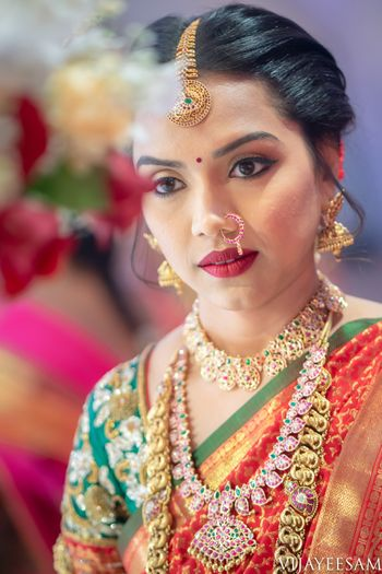 Layered south indian bridal jewellery with orange and green saree
