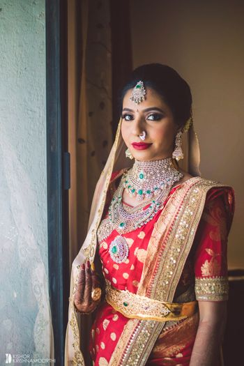 south indian bride in red kanjivaram with contrasting green jewellery