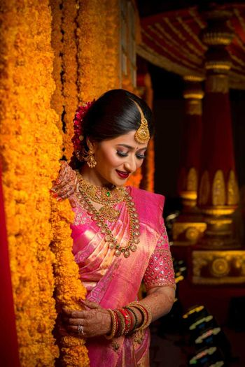 south indian bridal look with pink saree and layered jewellery