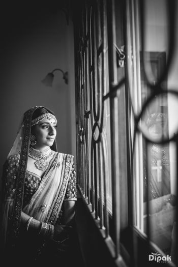 Bride looking out of window black and white shot
