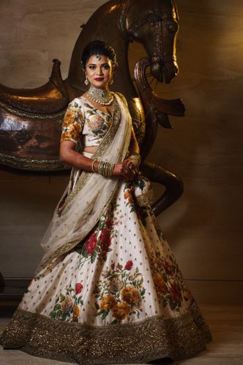White reception lehenga with floral work by Sabyasachi