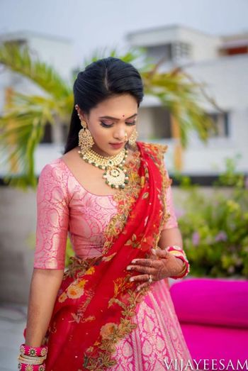 A bride in a pink lehenga with a contrasting dupatta