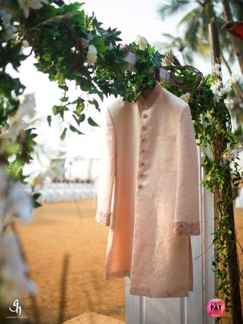 Light pink or peach sherwani on hanger