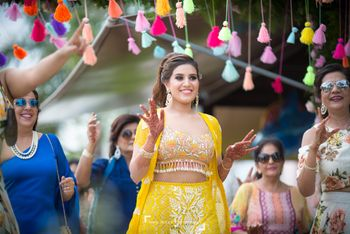 Bride in yellow outfit entering on engagement under tassel chadar