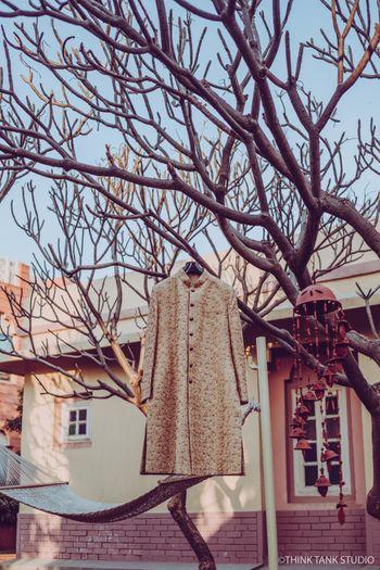 Cream sherwani hanging on tree
