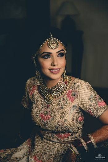 Bride getting ready shot in beige lehenga