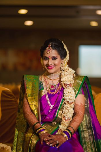 South Indian bride with floral braid hairstyle and kanjivaram saree