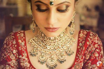 Contrast jewellery with red bridal lehenga
