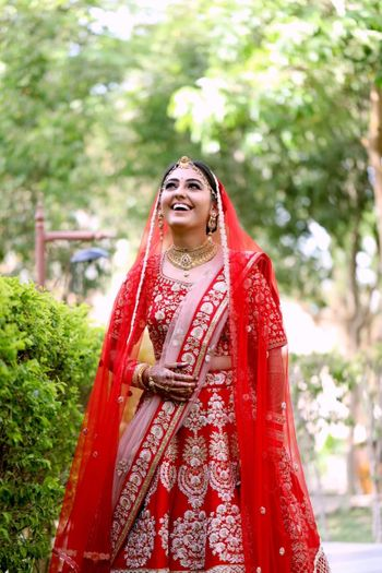 Red and pink bridal lehenga with happy bride