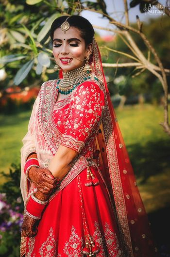 Pretty bridal portrait with red lehenga and emerald jewellery