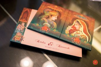 Photo of Modern Mughal theme wedding card with bride and groom portraits