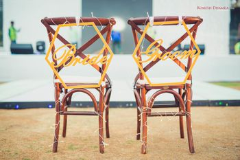 Bride and groom chair decor idea with signs