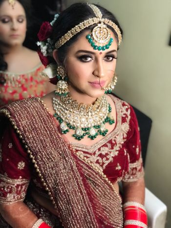 Velvet maroon lehenga with oversized emerald jewellery
