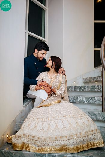 Stunning couple portrait with bride in white and gold lehenga