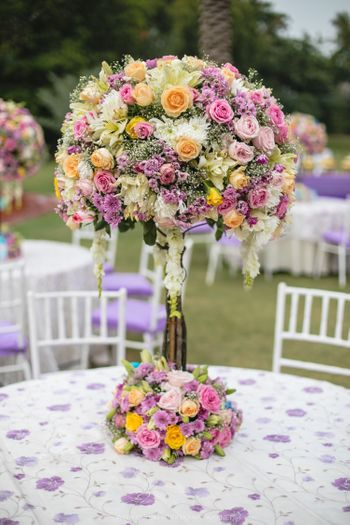 Photo of Stunning colourful table pieces with flowers