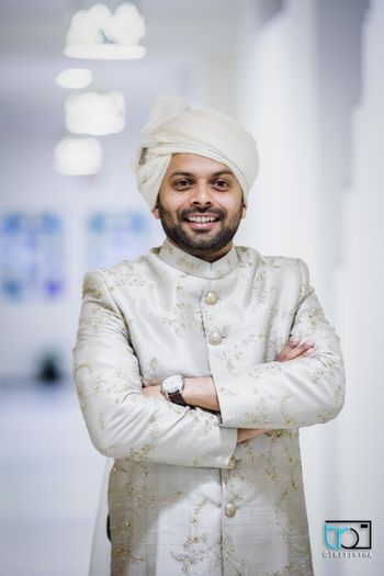 Monotone groom in ivory sherwani and safa