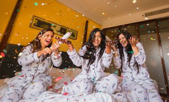 Photo of Bride and bridesmaids in matching pyjamas with confetti