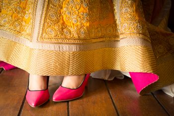 Photo of pink stilletoes peep toes under yellow lehenga
