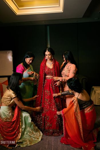 Stunning bride in red lehenga getting ready with bride