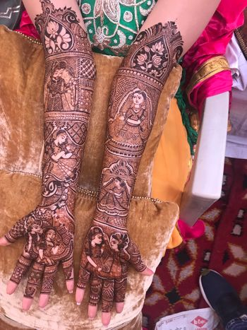Gorgeous intricate mehendi with bride and groom caricatures.
