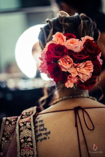 Offbeat bridal bun with big flowers